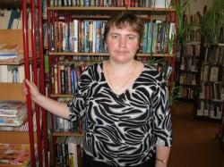 молодая женщина стоит у стеллажа с книгами